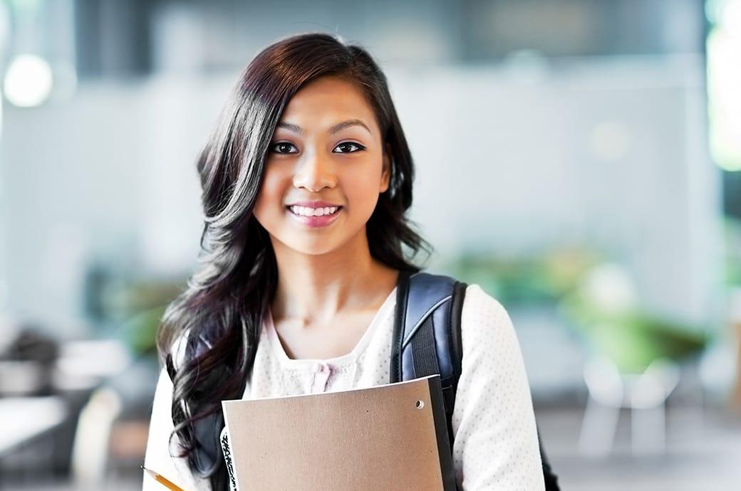 Adolescente con lentillas sonriente con mochila y cuadernos.