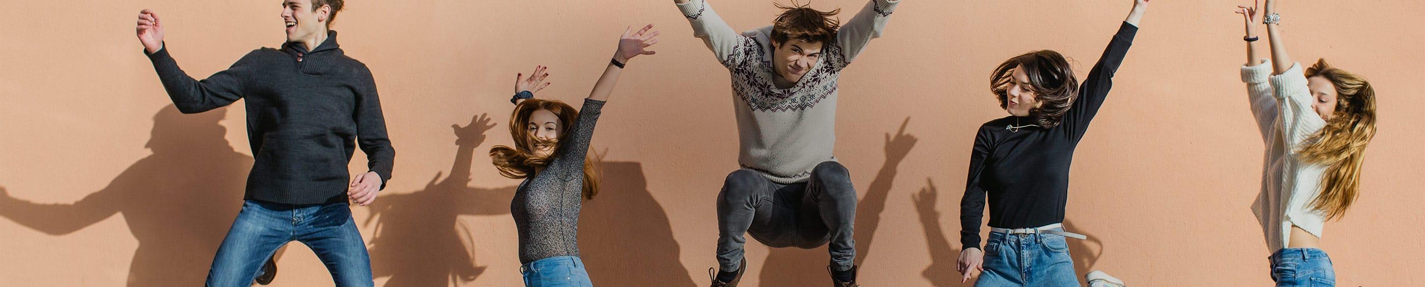 Una foto perfectamente sincronizada de un grupo de amigos que llevan lentillas que saltan en el aire con las manos en alto.