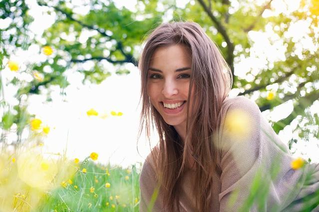 Chica con lentillas sonriendo tendida en el césped de un día soleado.