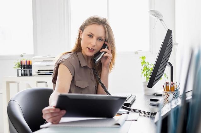 Una mujer con lentillas en su escritorio mirando una Tablet mientras habla por teléfono.