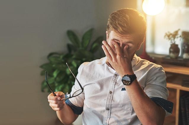 Imagen de un hombre quitándose las gafas para frotarse los ojos