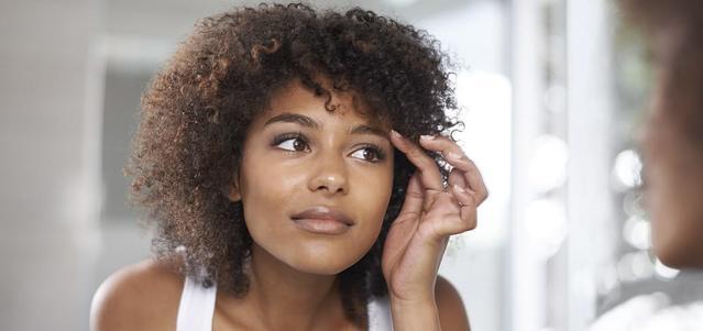 Chica al espejo observando como le quedan de natural y bien las lentillas
