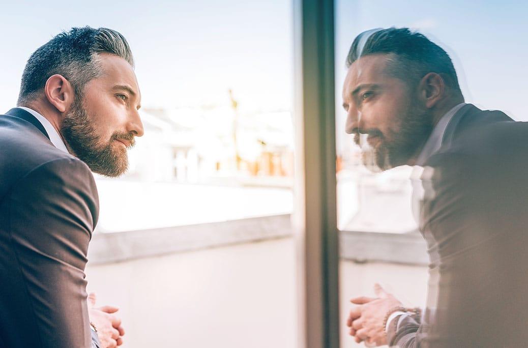 Imagen de un hombre mayor con lentillas mirándose su reflejo en la ventana