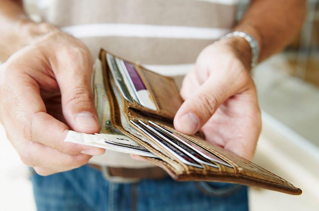 Primer plano de alguien con lentillas sacando billetes de una billetera