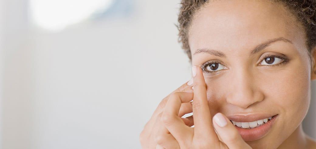 Una chica con una lentilla en su dedo a punto de ponerla en el ojo