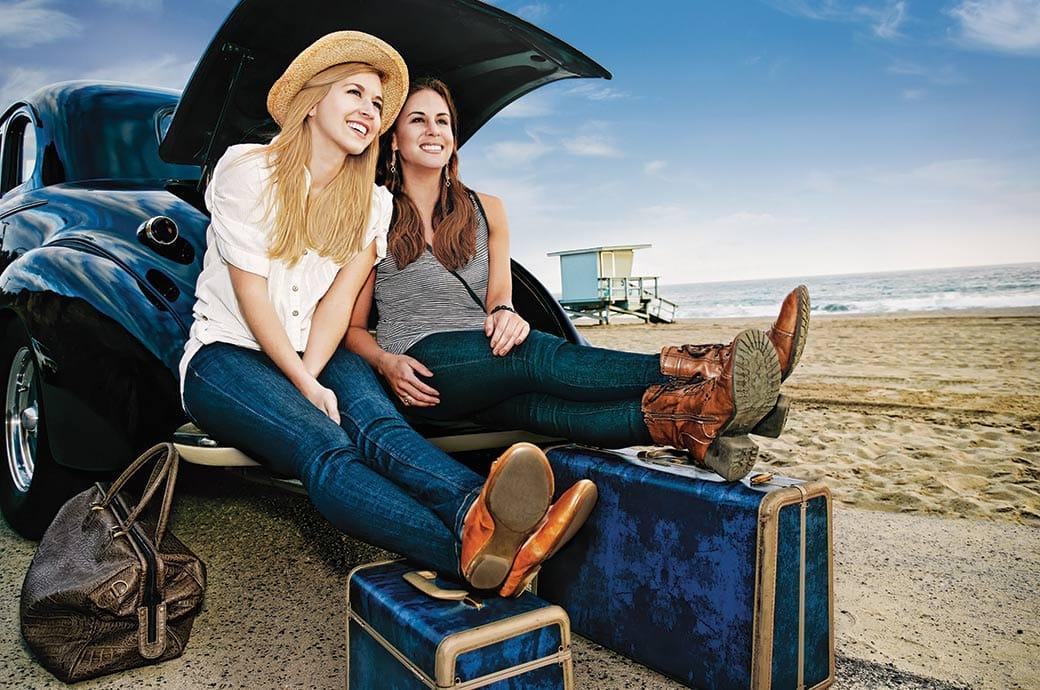 Dos chicas con lentillas sentadas en el maletero de un coche con su equipaje preparado para irse de vacaciones.